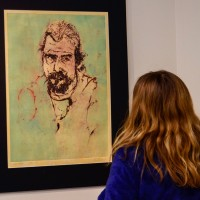 A viewer admires Adam Rake's self portrait.
